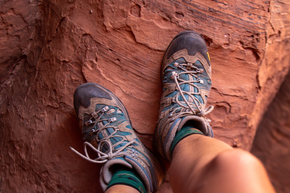 person wearing black and gray hiking shoes