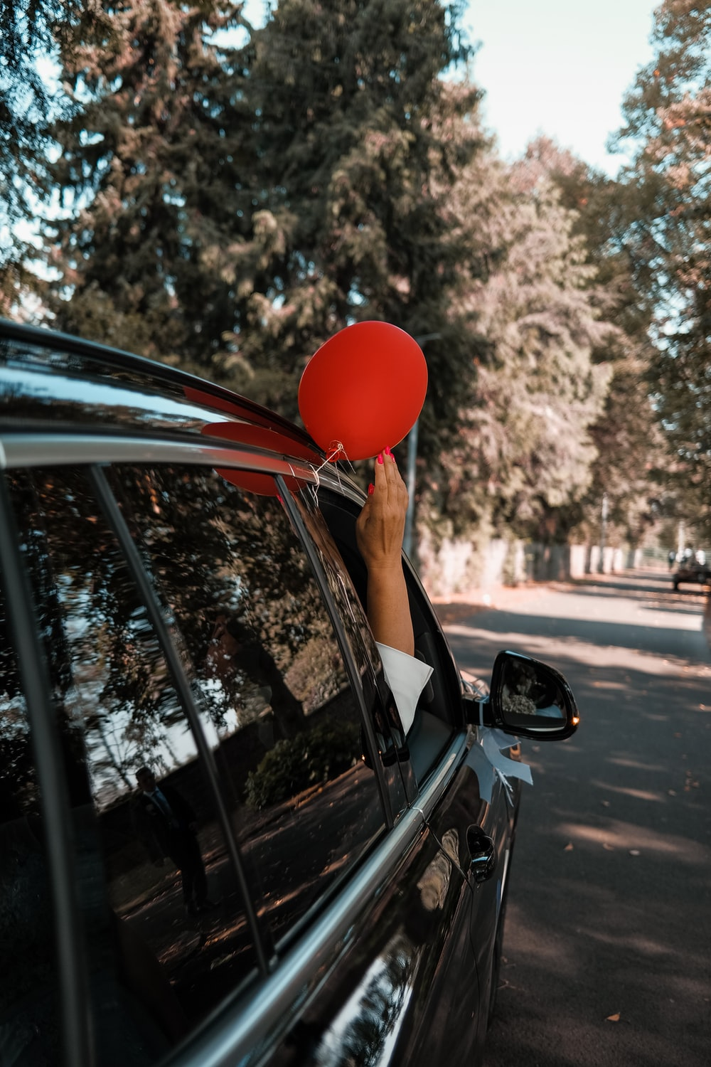 person holding red balloon in car
