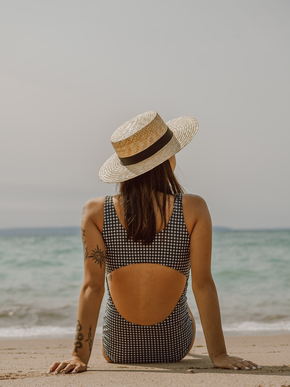 woman in black and white polka dot bikini wearing brown sun hat standing on beach during