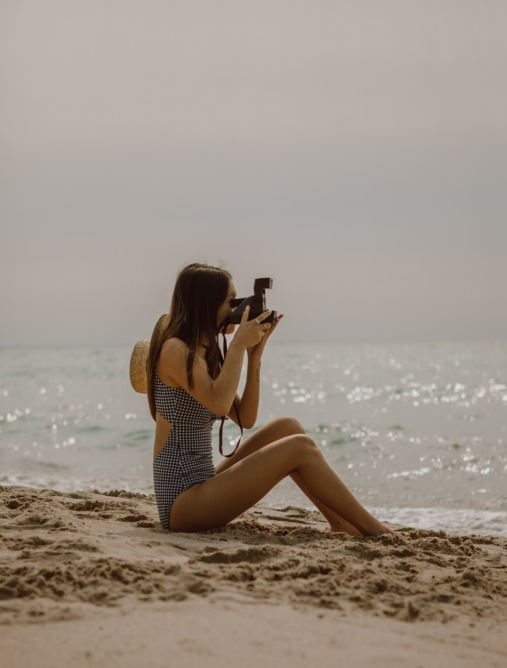 woman in black and white polka dot swimsuit sitting on beach shore during daytime