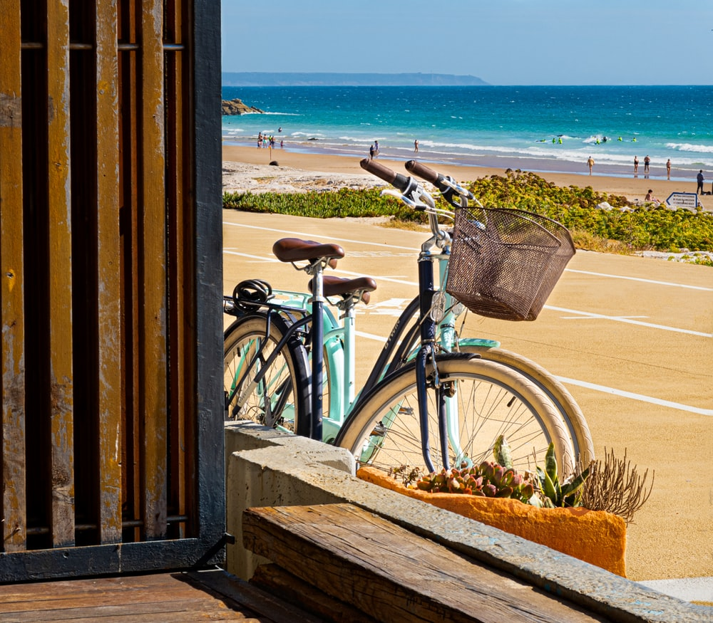 blue city bike on wooden fence near sea during daytime