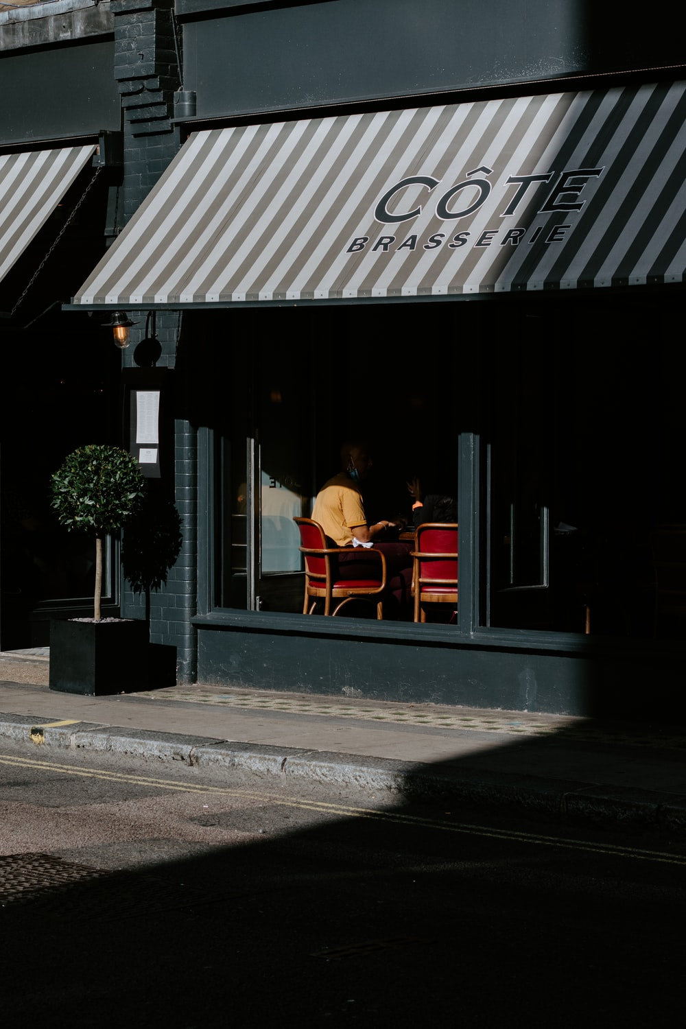 2 person sitting on chair in front of black and white store during daytime