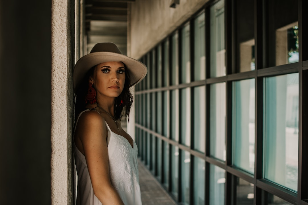 Woman In White Spaghetti Strap Dress Wearing Brown Hat Standing In Front of Blue Metal Gate - unsplash