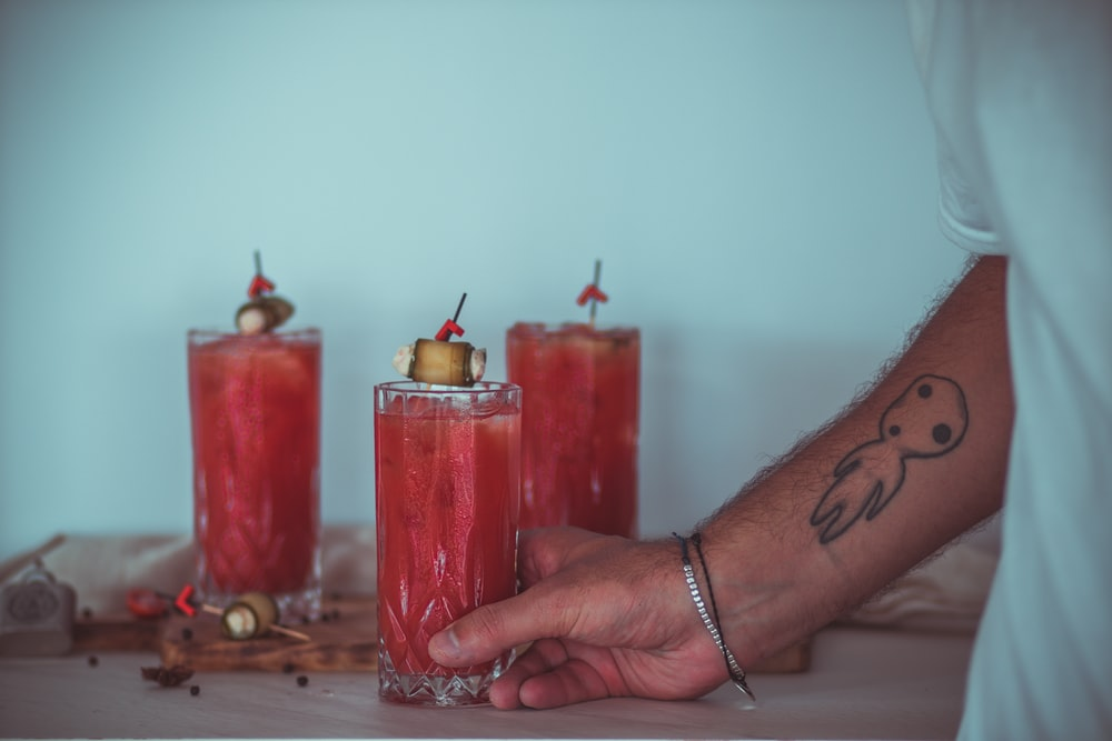 person holding red pillar candles