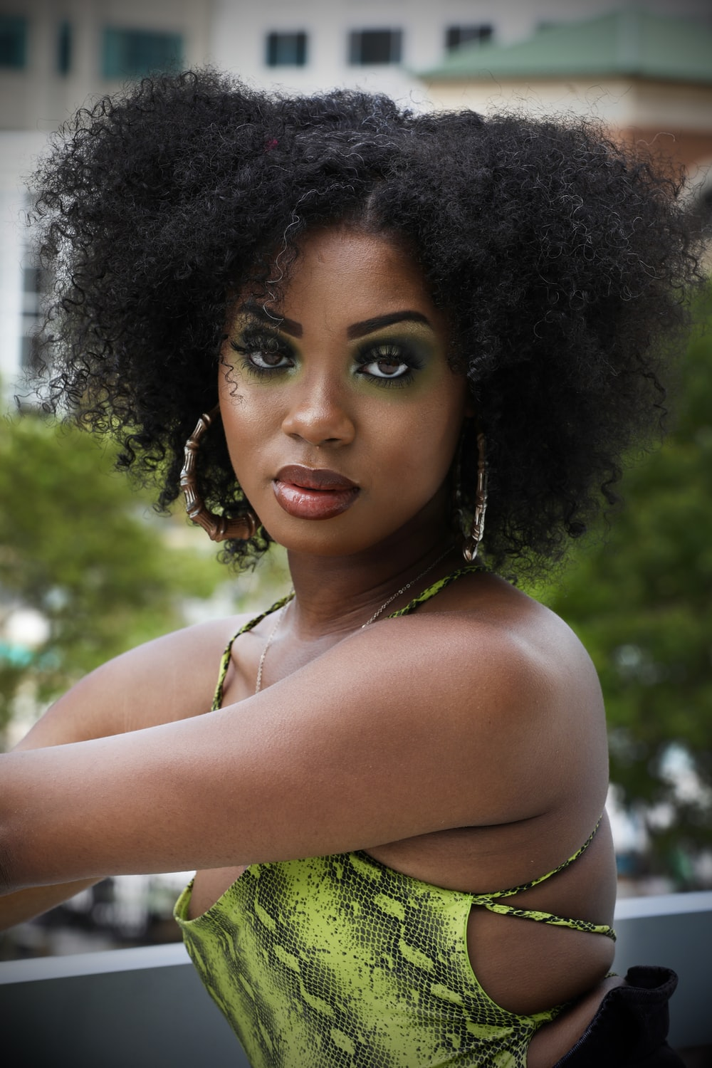 woman in white tank top with black curly hair