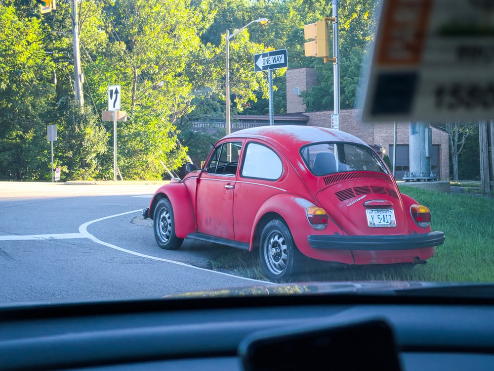 red volkswagen beetle on road during daytime