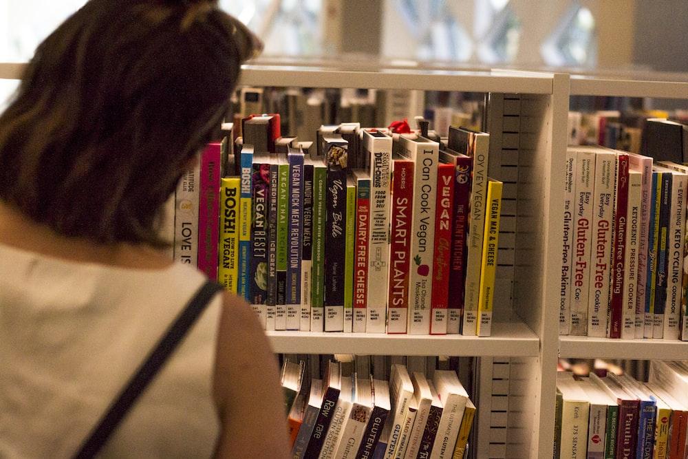 woman in black tank top standing near books