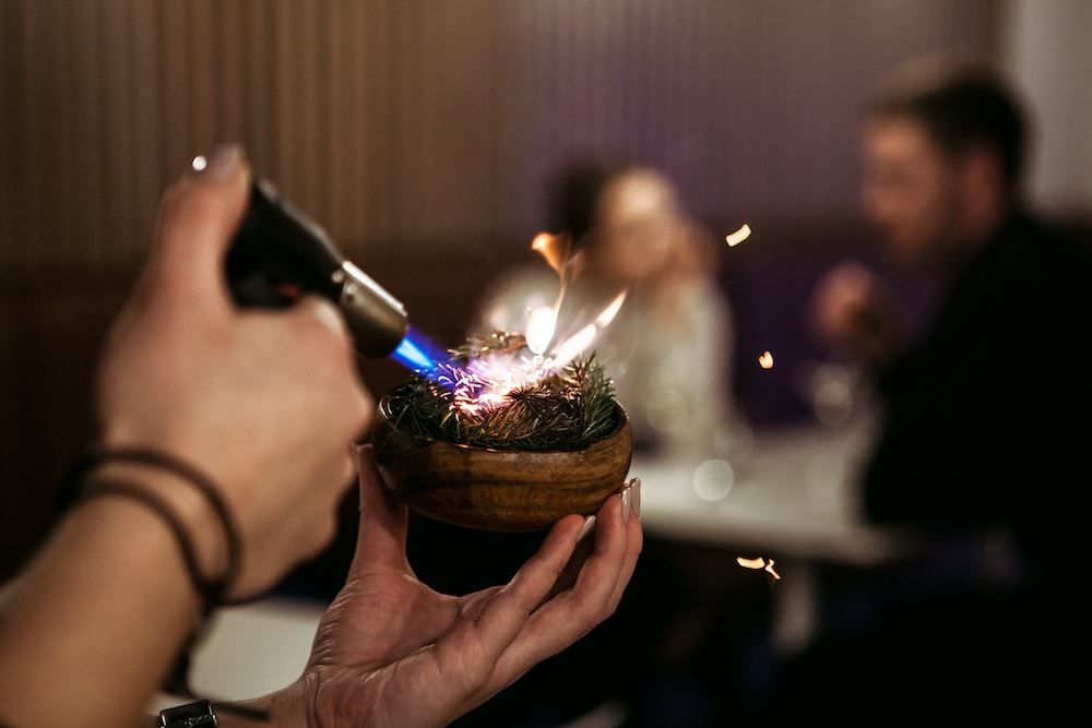 person holding lighted candle in brown round container