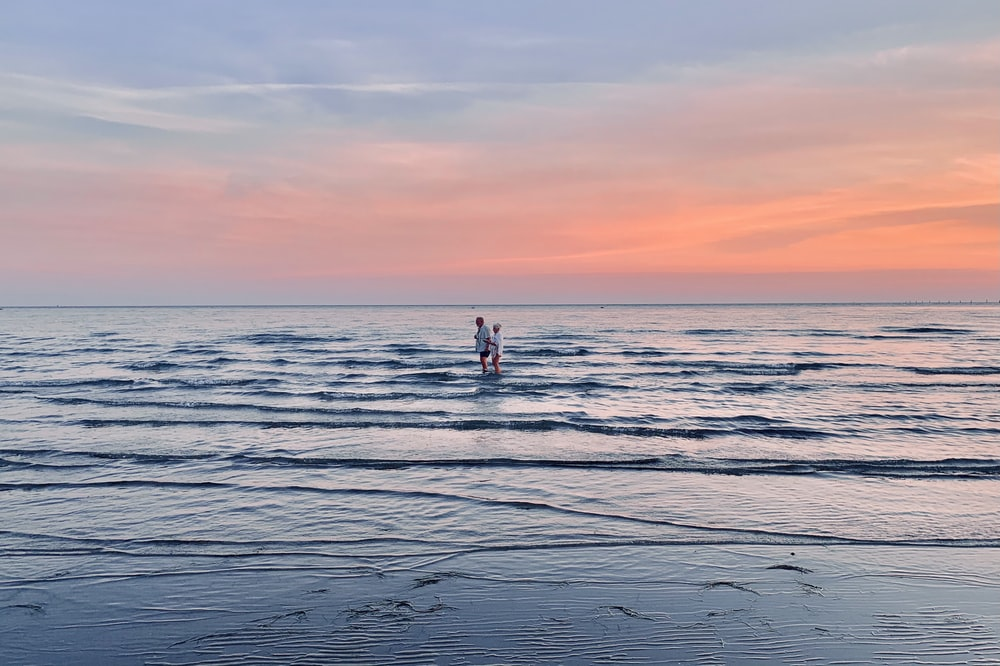 2 person standing on sea shore during sunset