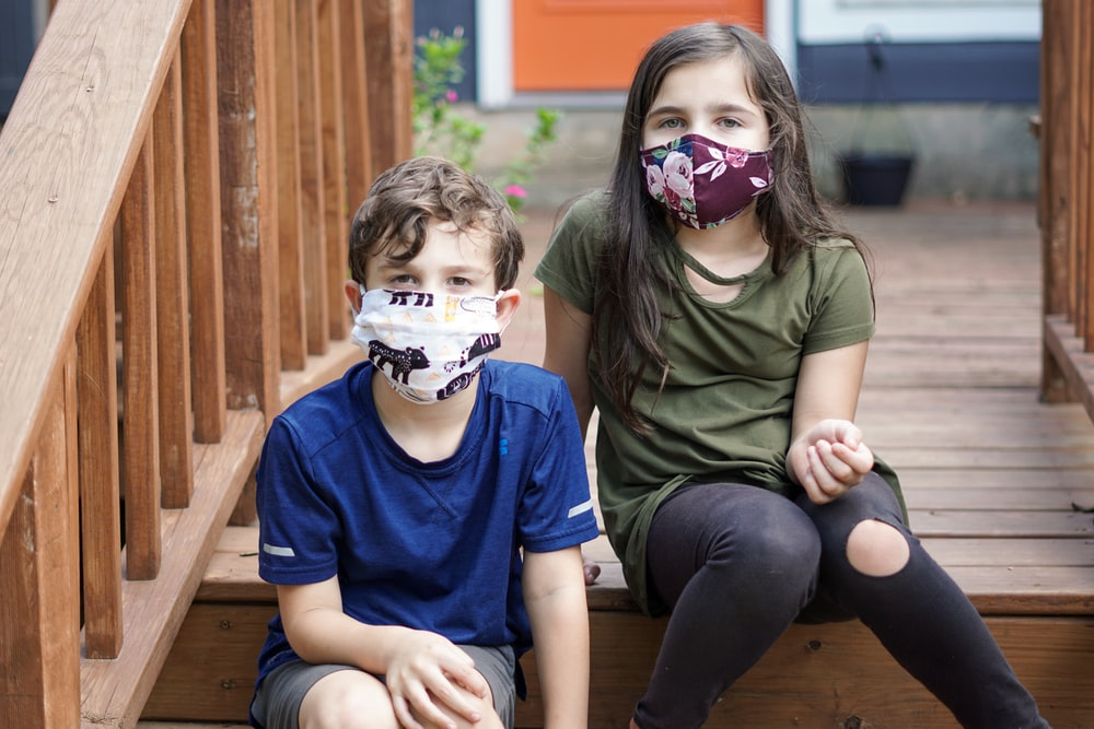 boy in green crew neck t-shirt sitting beside girl in white mask