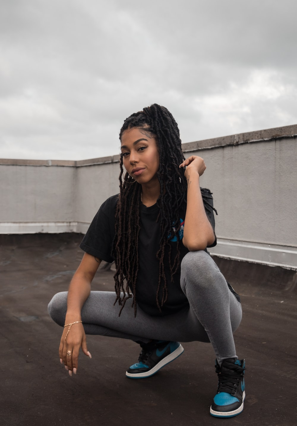 woman in black t-shirt and gray pants sitting on concrete wall during daytime