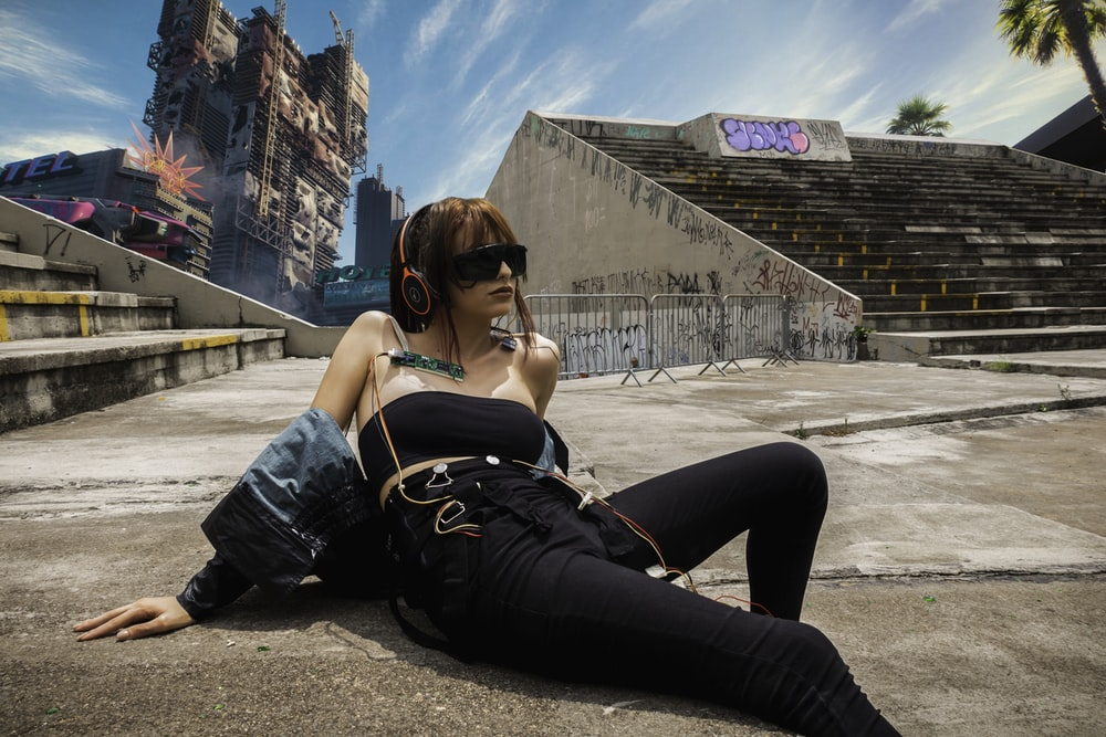 woman in black denim jeans and black sunglasses sitting on gray concrete floor during daytime