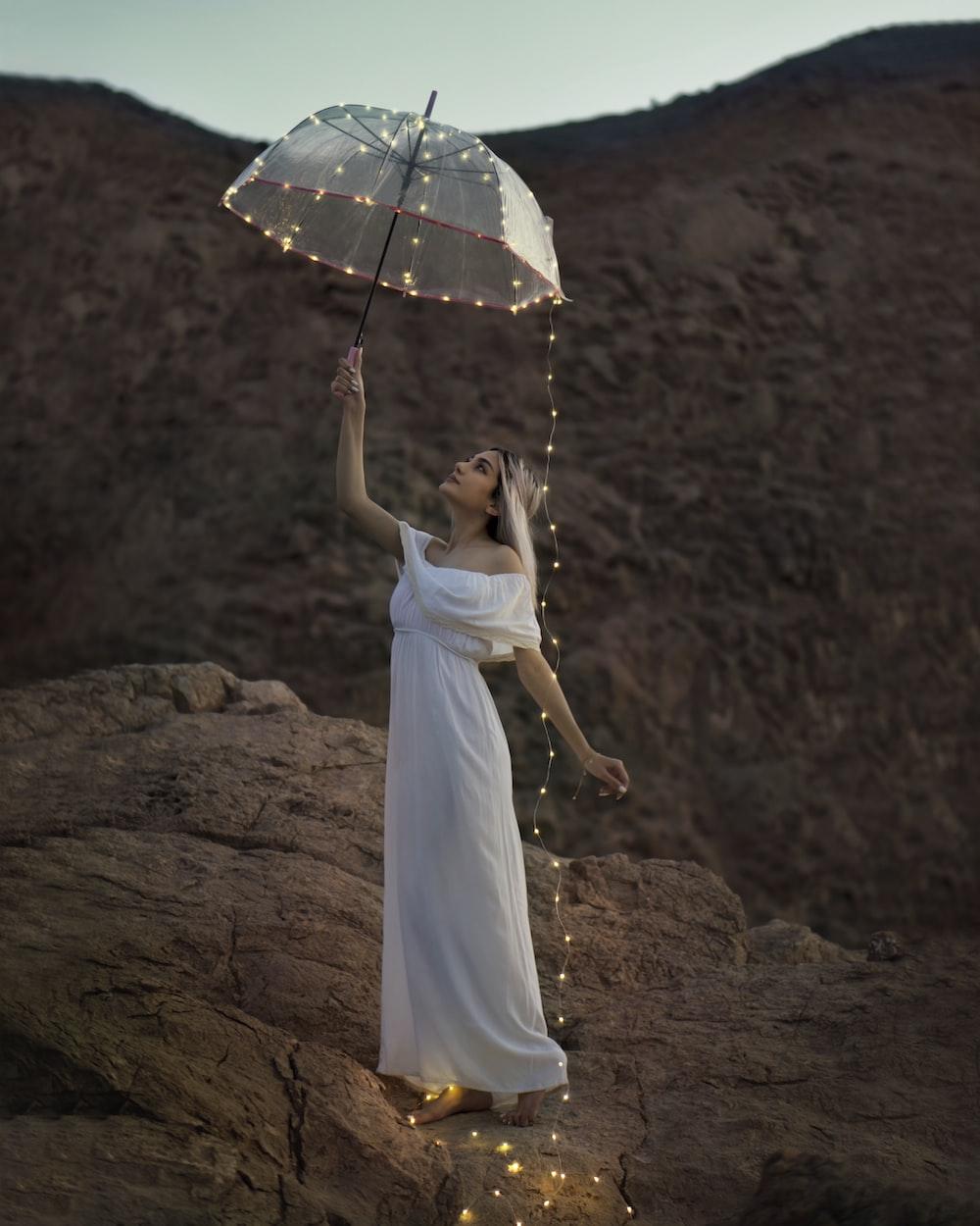woman in white dress holding umbrella