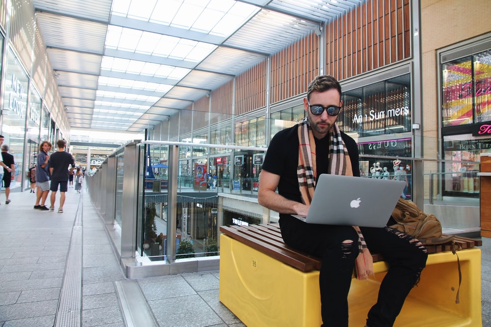 woman in black shirt and yellow pants holding silver macbook