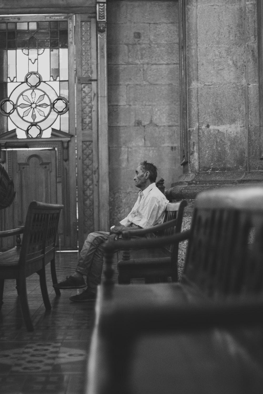 man in white dress shirt sitting on chair