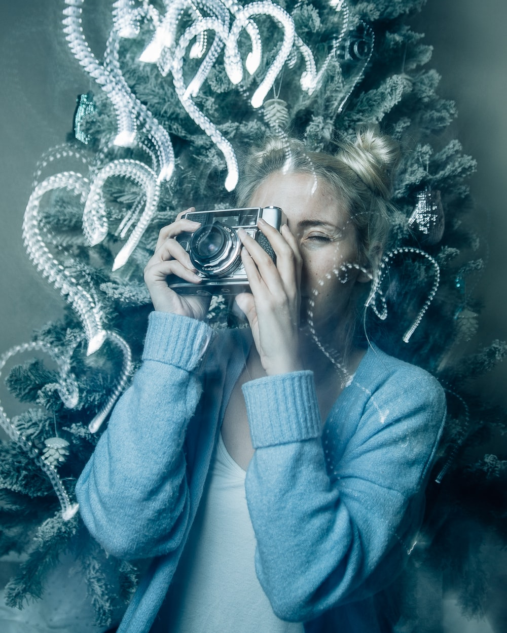 woman in blue sweater holding black camera
