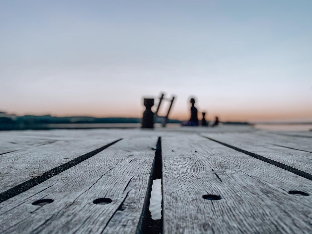 people walking on wooden dock during sunset