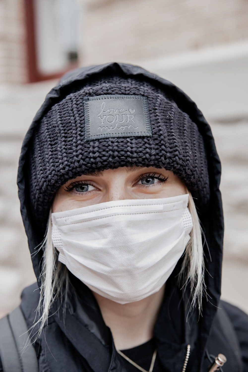 woman in black knit cap and white face mask