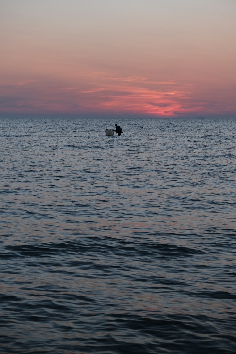 silhouette of person on boat on sea during sunset