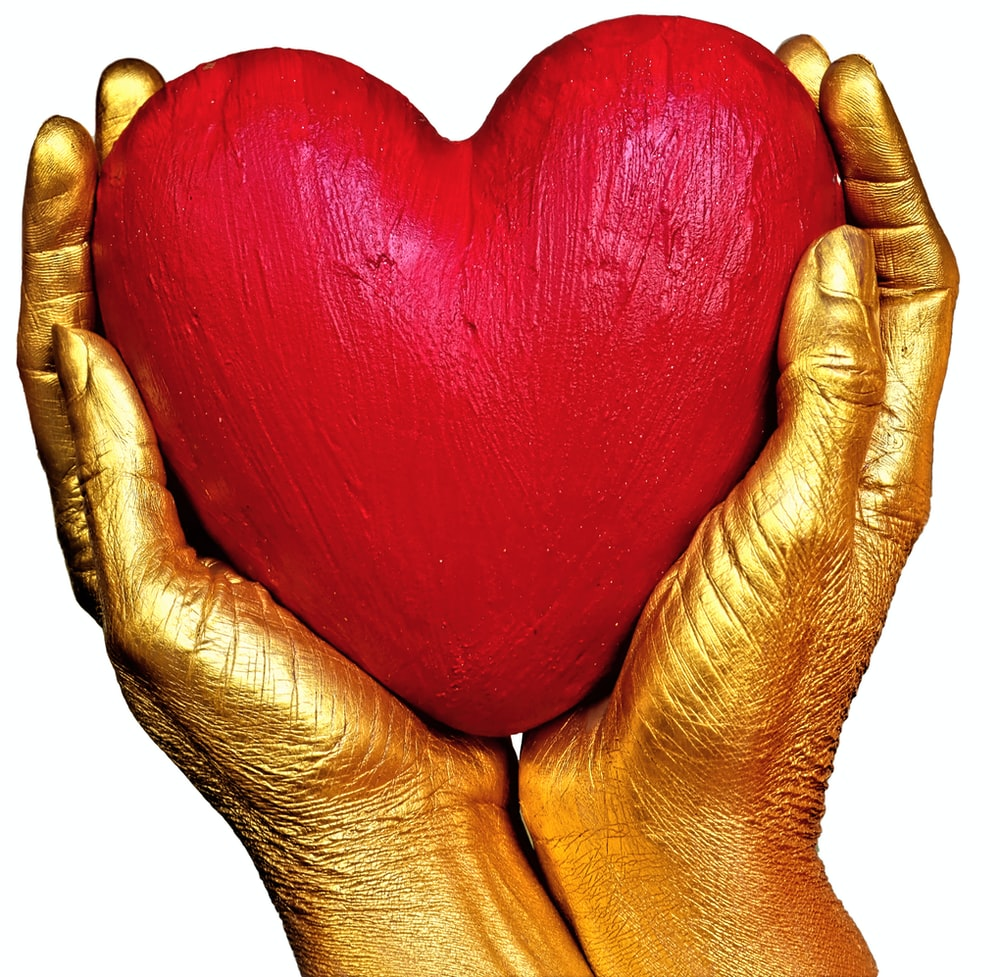 person holding red heart shaped ornament