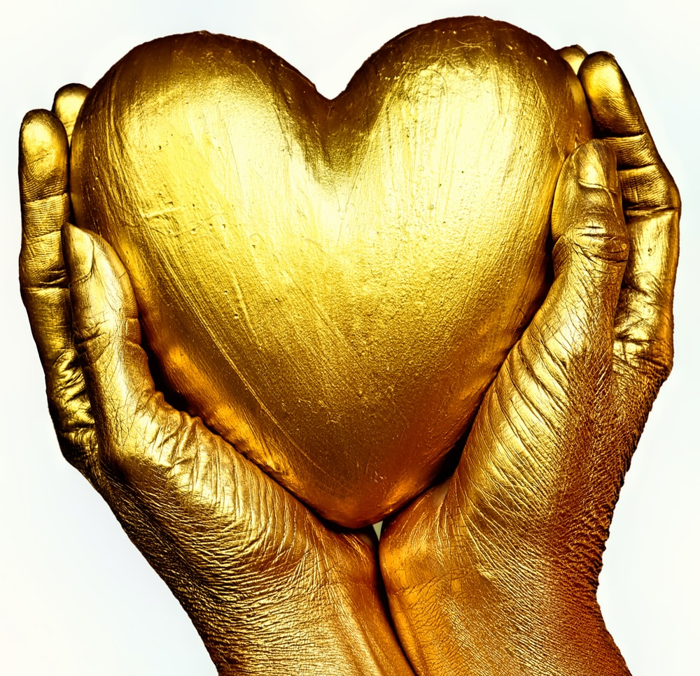 gold heart shaped ornament on persons hand