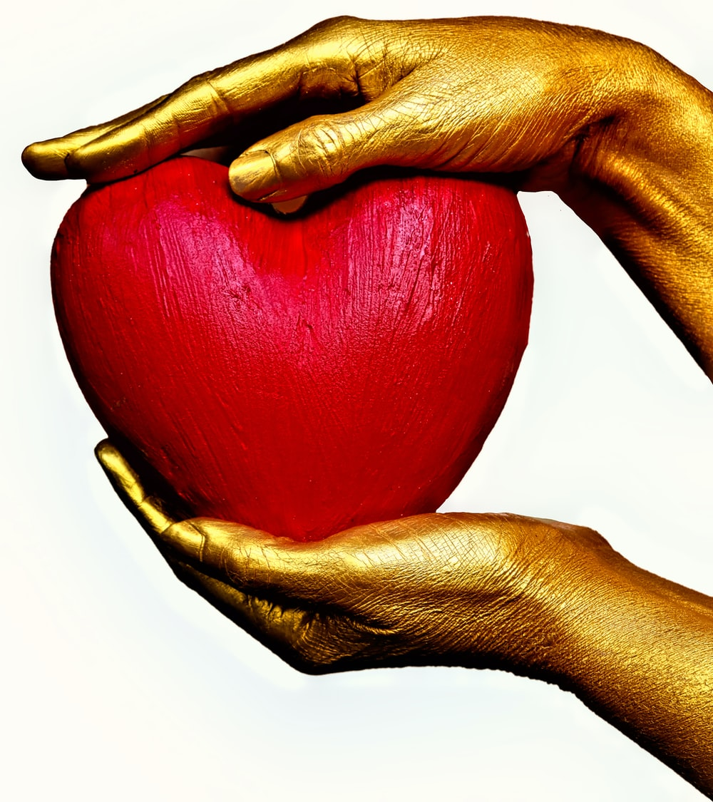 person holding red heart ornament