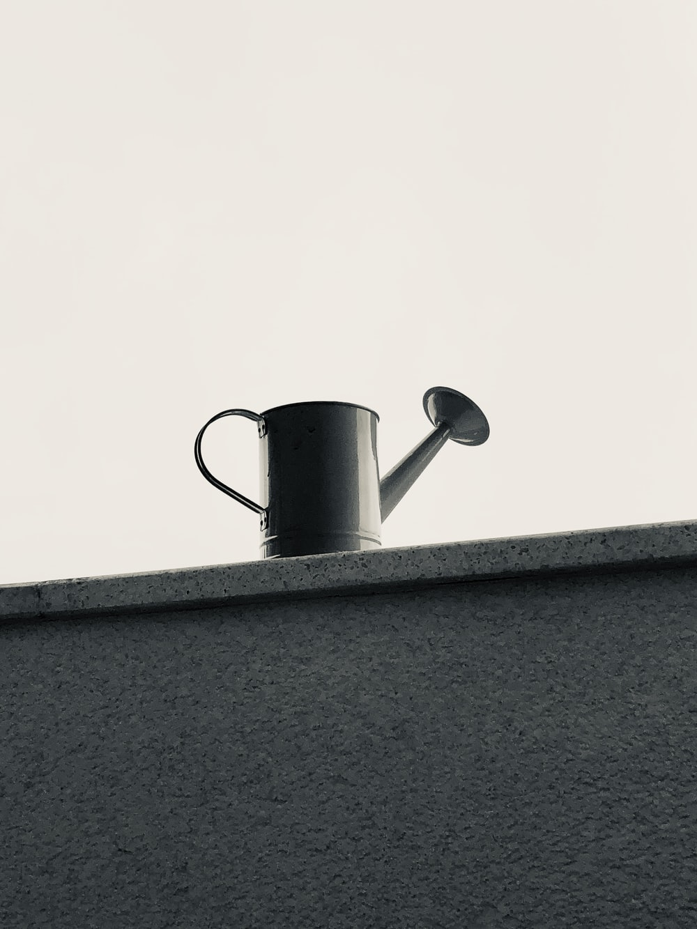 black and white ceramic mug on gray concrete wall