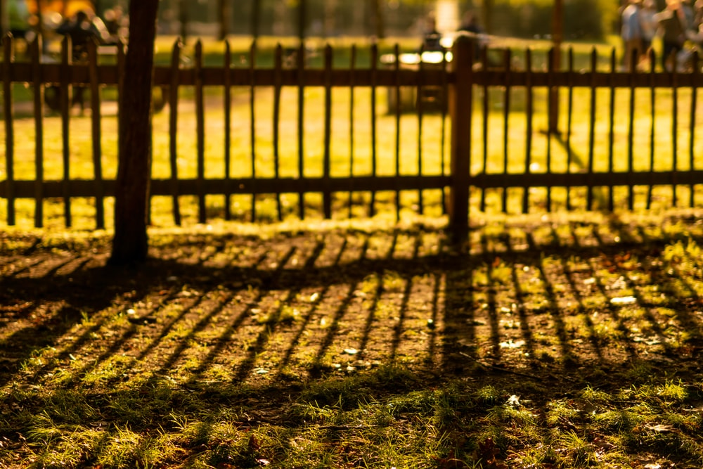 brown wooden fence on green grass field during daytime