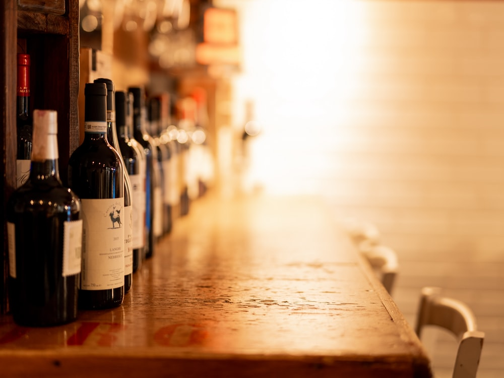 selective focus photography of wine bottles on wooden table