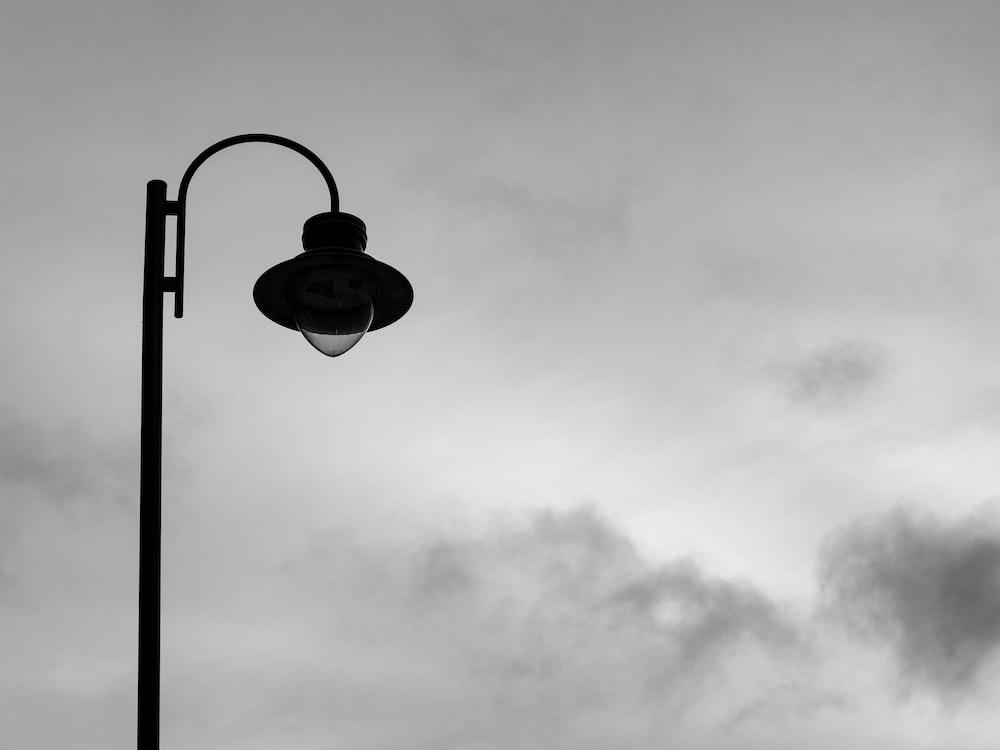 grayscale photo of light bulb under cloudy sky