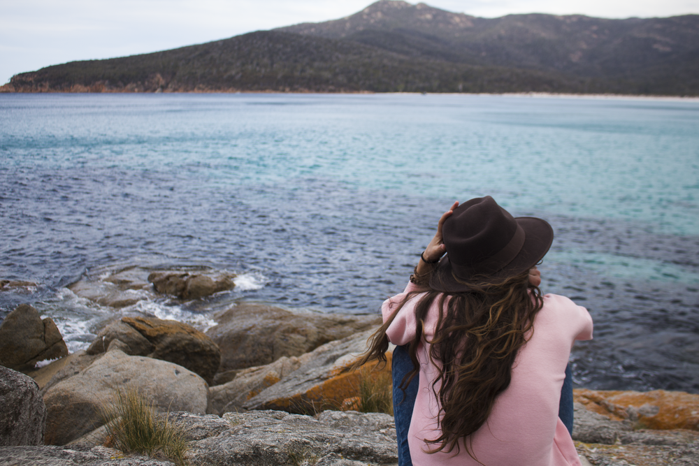 woman in blue tank top and brown fedora hat sitting on rock near body of water