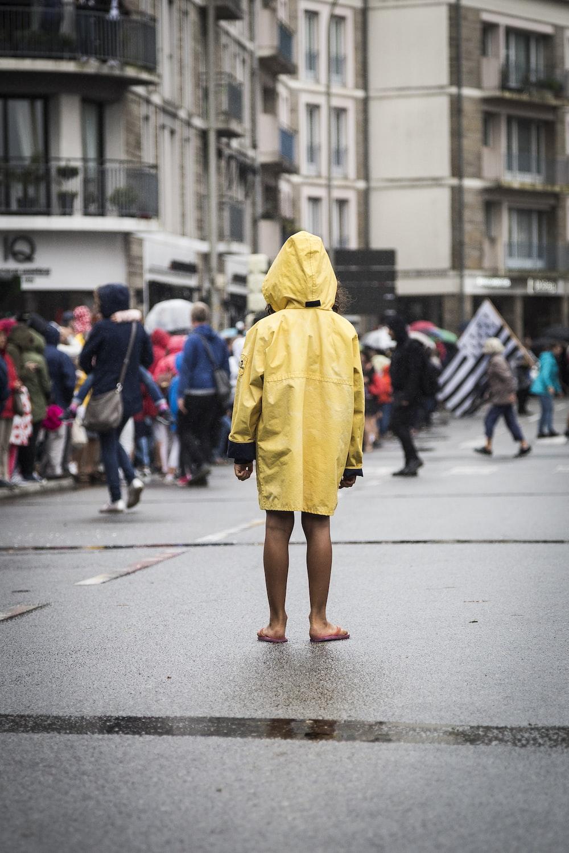 woman in yellow coat walking on street during daytime