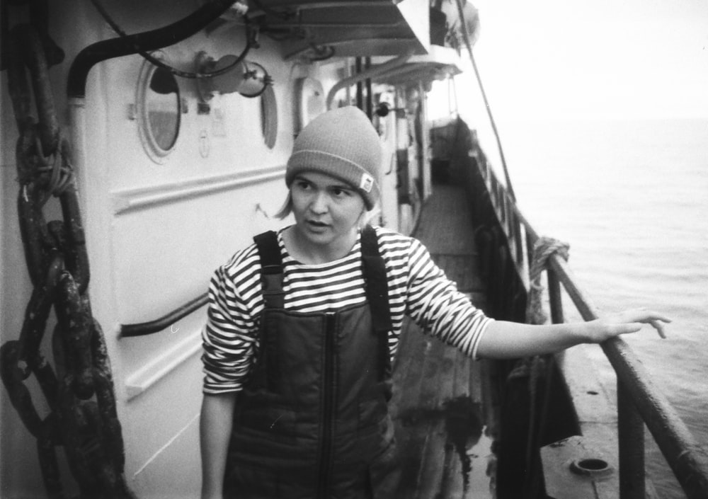 grayscale photo of man in black jacket and knit cap standing on boat