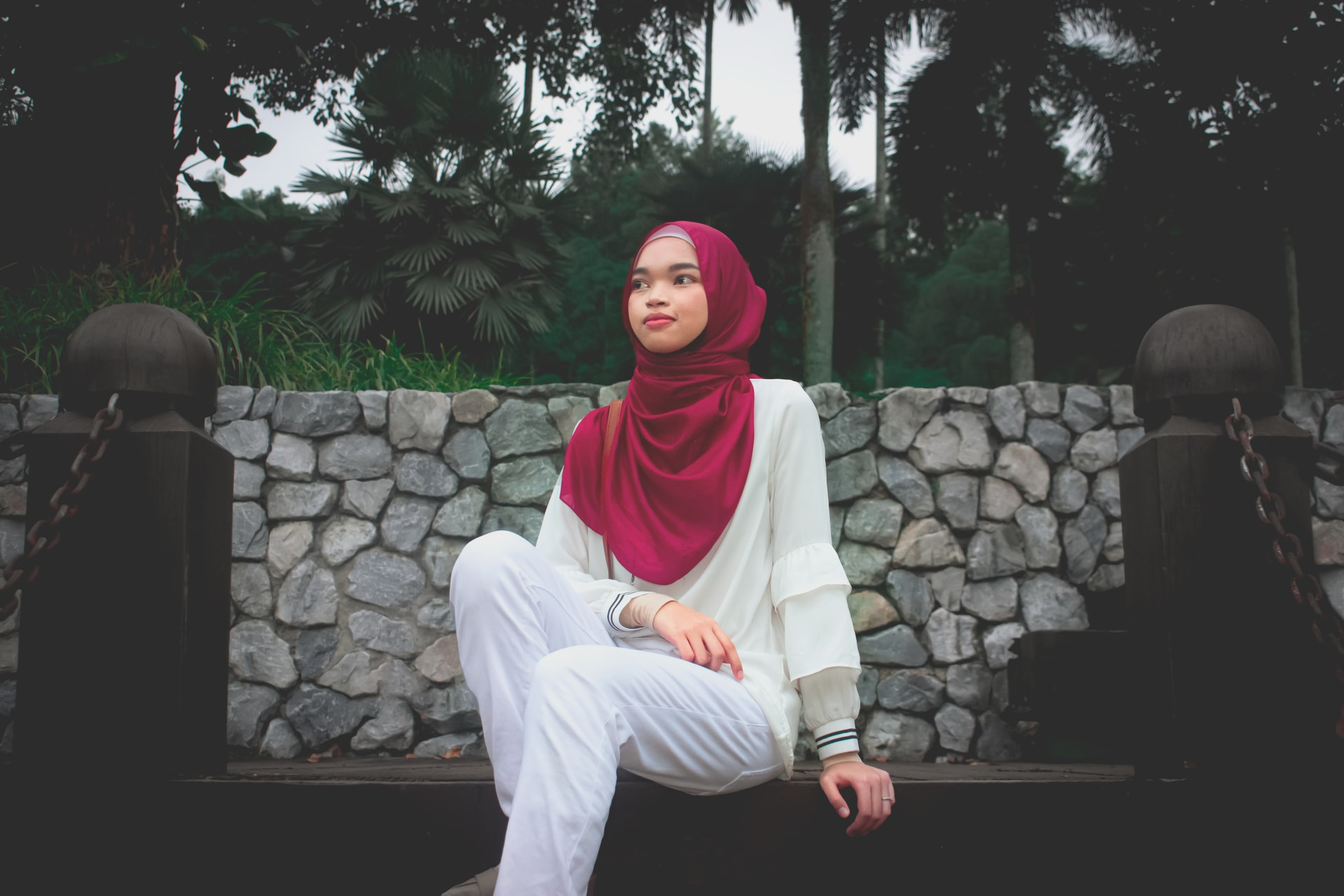 woman in white long sleeve shirt and red hijab sitting on brown wooden bench