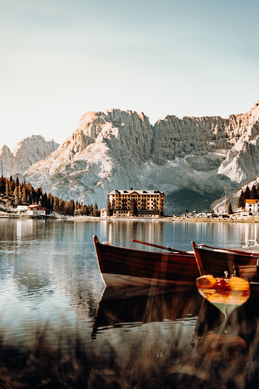 brown wooden boat on lake near mountain during daytime