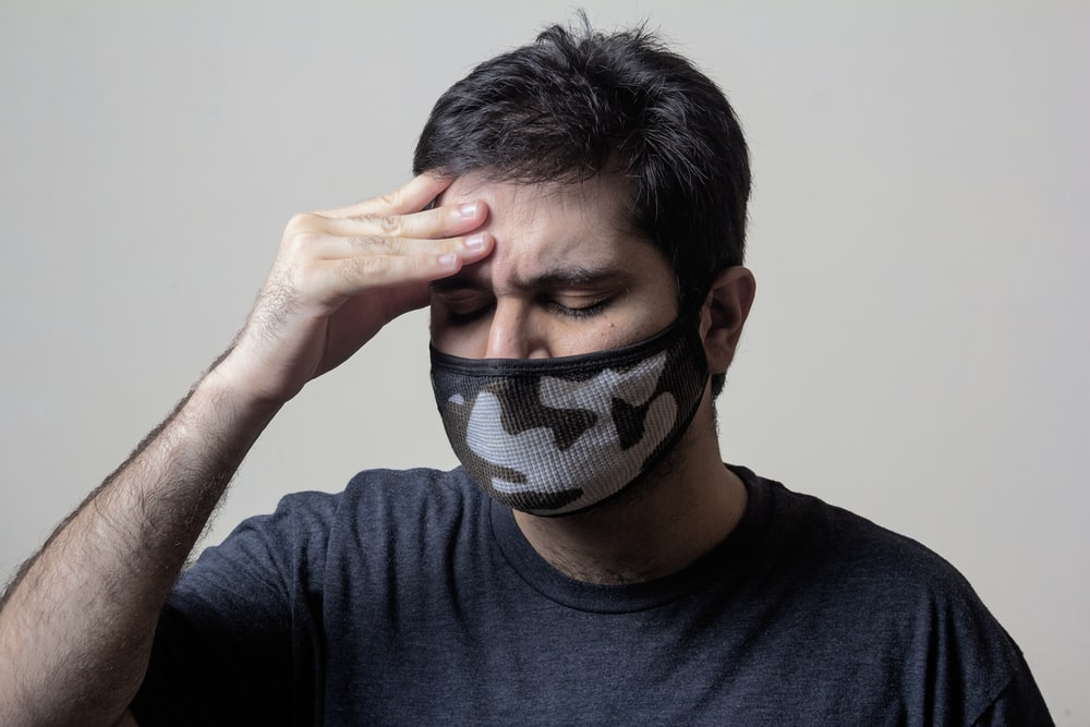 man in black crew neck shirt covering his face with black and white textile