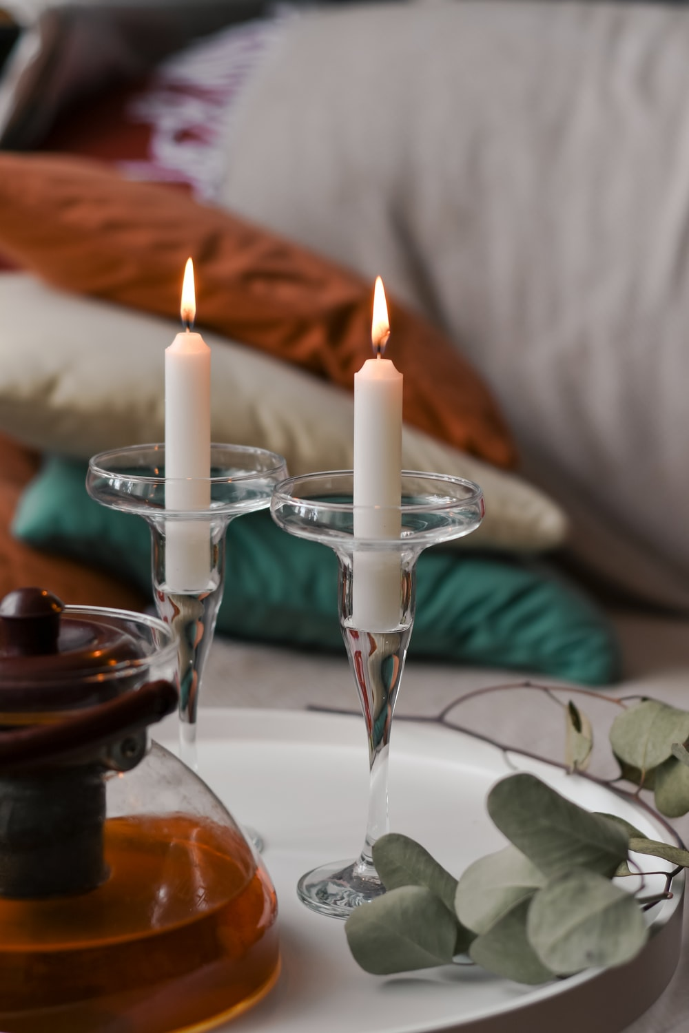 white candles on clear glass candle holder