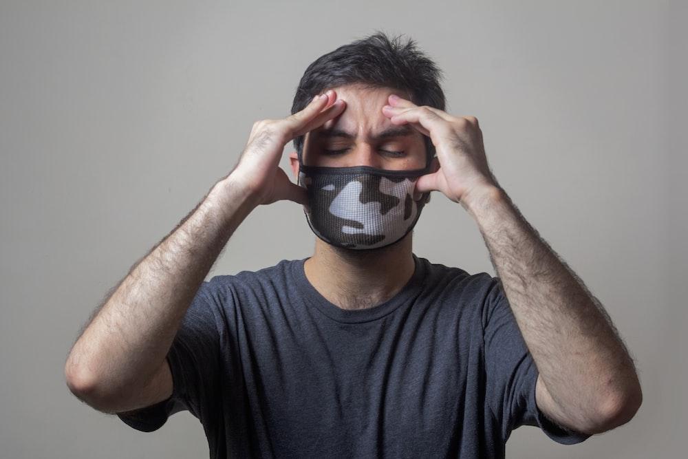 黒と白のマスクを身に着けている黒のクルーネックTシャツの男