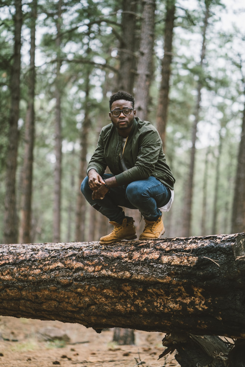 man in green jacket and blue denim jeans sitting on brown tree log