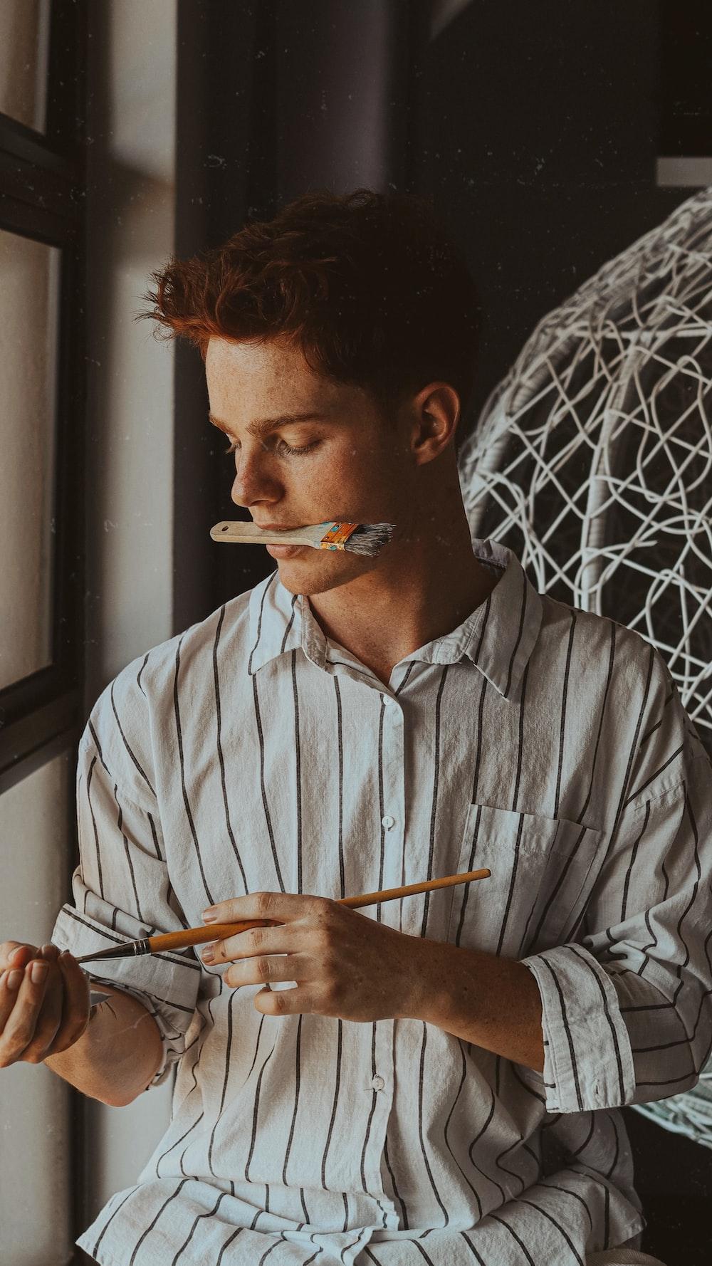 man in white dress shirt smoking cigarette