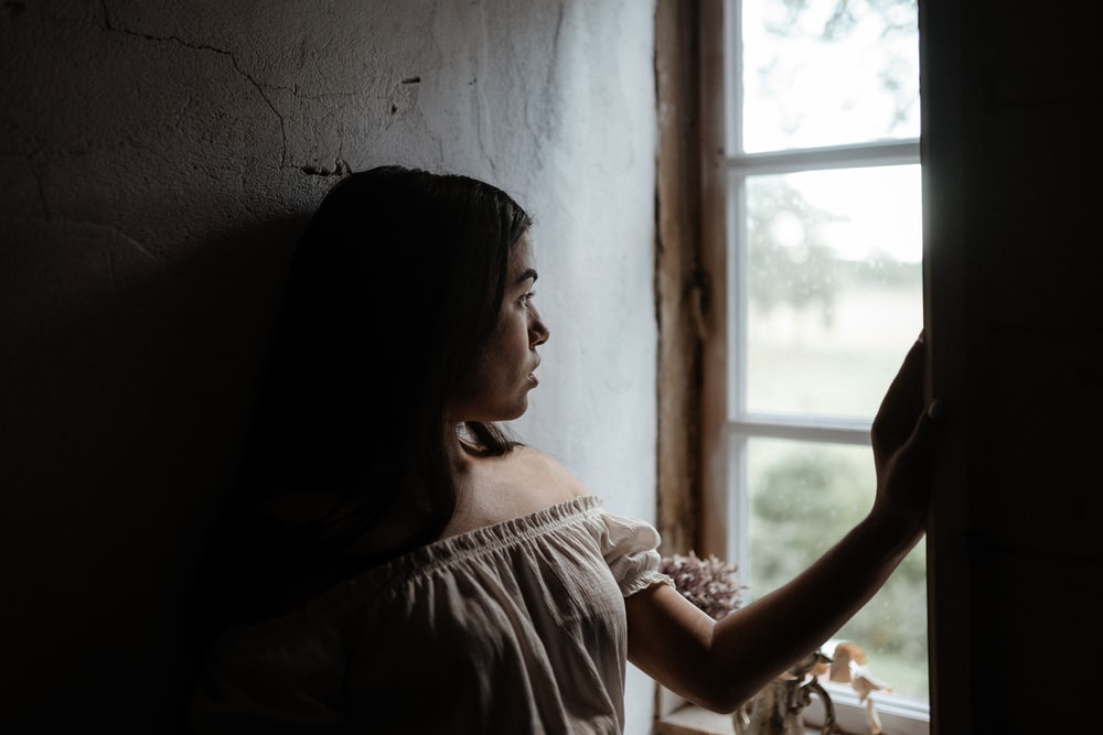 woman in white shirt standing near window during daytime