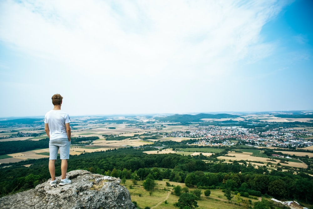 man in white t-shirt standing on rock formation looking at the city during daytime