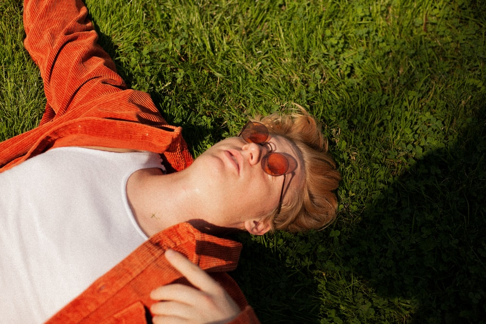 woman in red jacket lying on green grass field during daytime