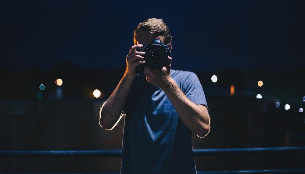 man in black t-shirt holding black dslr camera