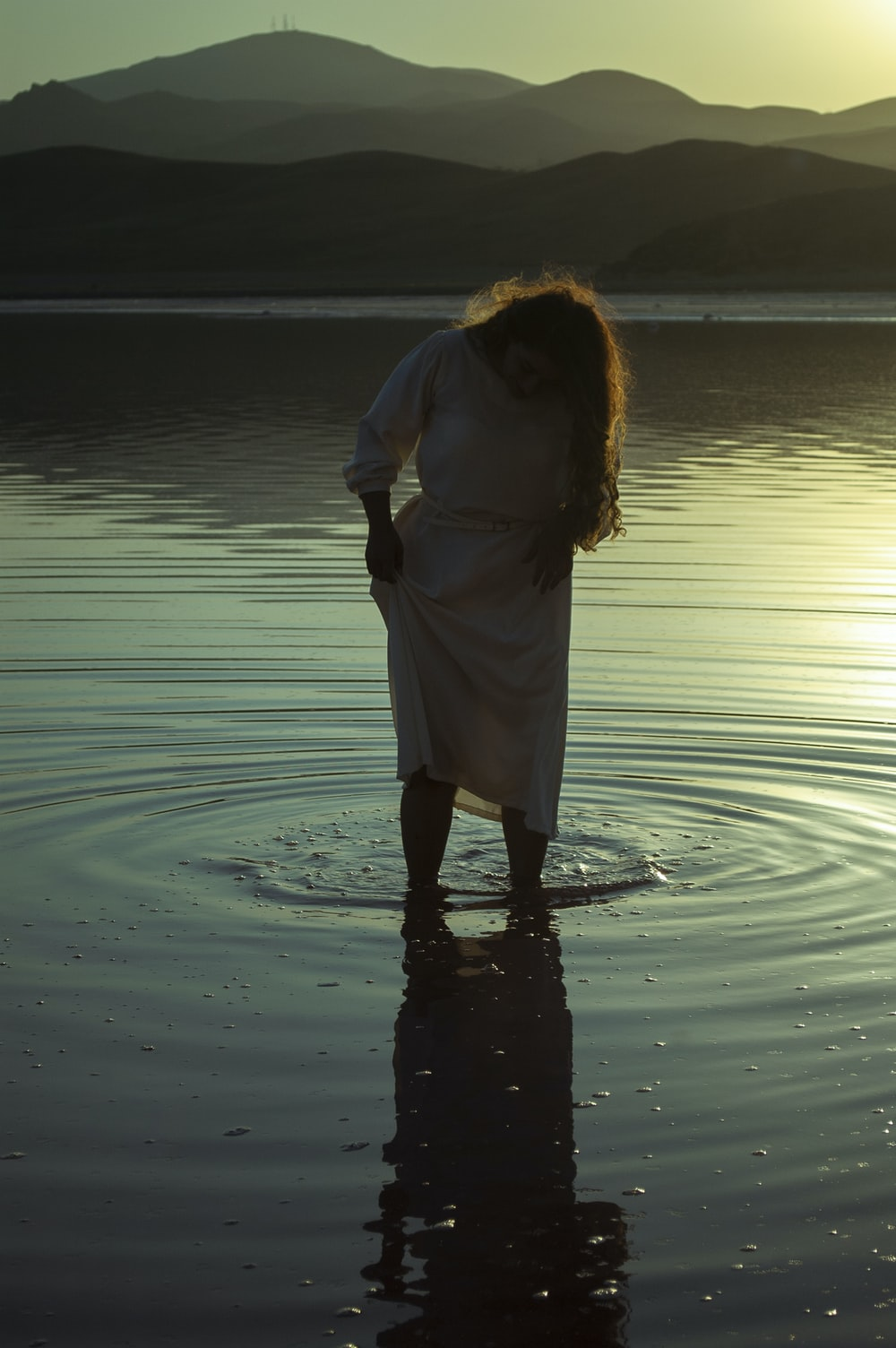woman in white dress standing on water during daytime