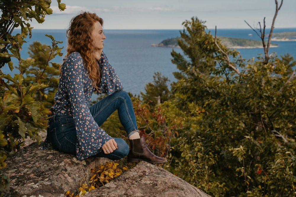 woman in blue and white long sleeve shirt and blue denim jeans sitting on rock near near near near near