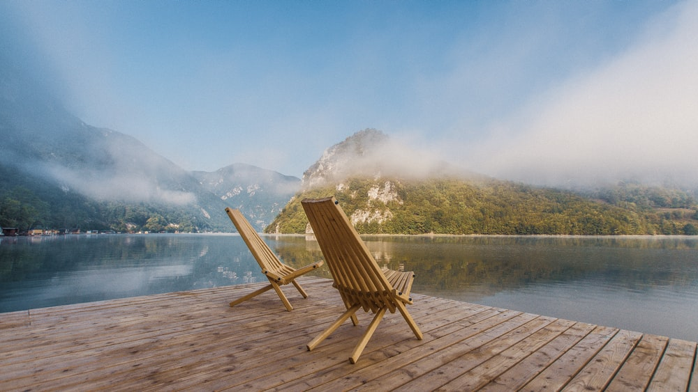 brown wooden chair on dock near lake during daytime