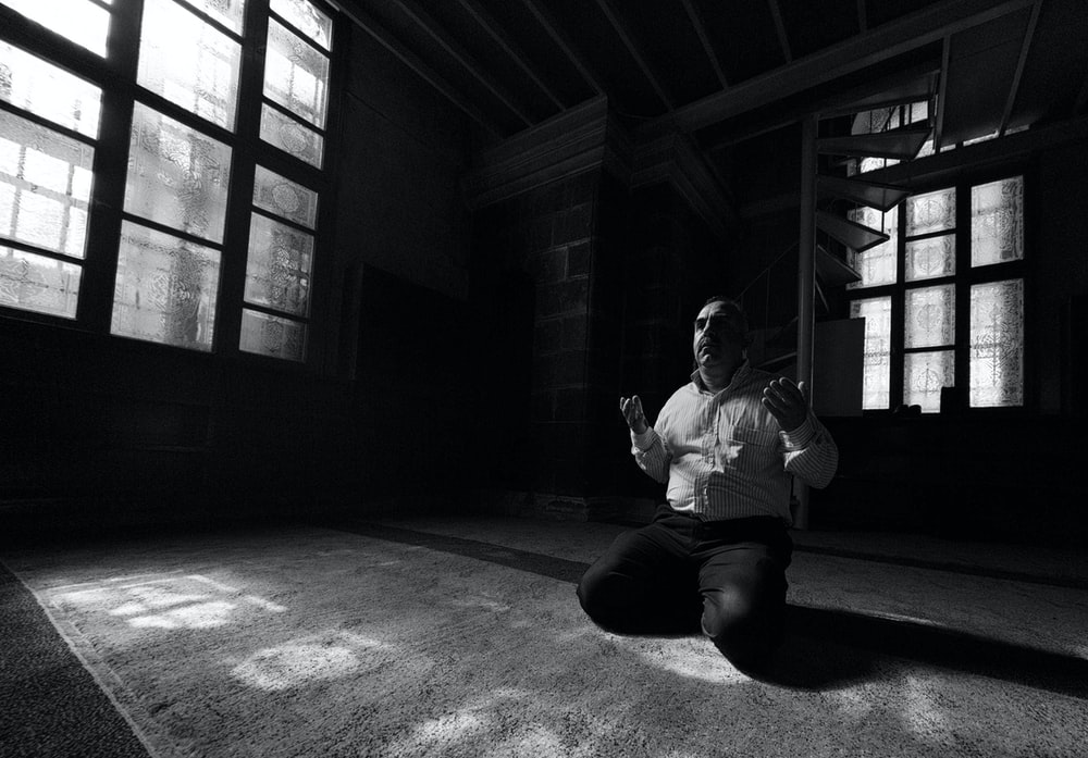 man in white dress shirt and black pants sitting on floor