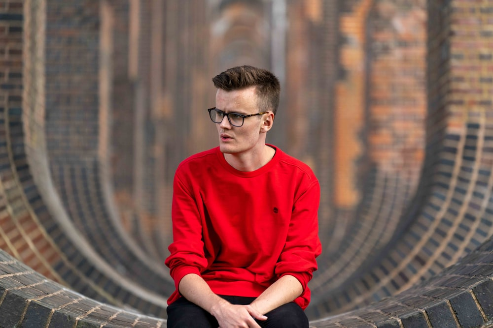 man in red sweater sitting on the ground