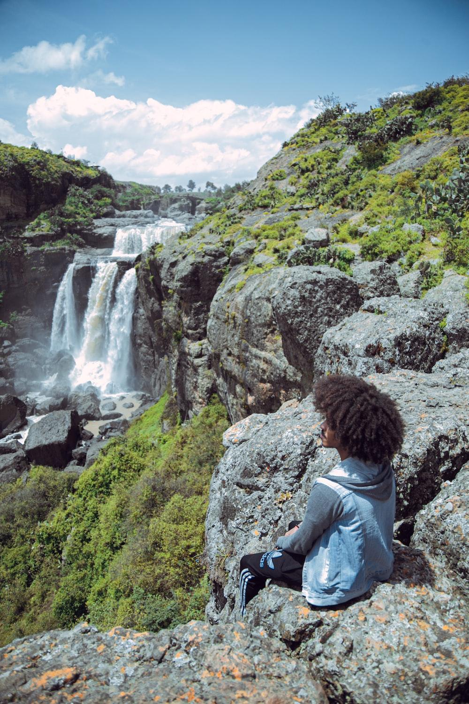 man in gray jacket sitting on rock looking at waterfalls during daytime